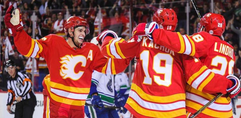 Sean Monahan, Matthew Tkachuk, and Elias Lindholm celebrate after Lindholm scored the game-winning goal against Vancouver Canucks