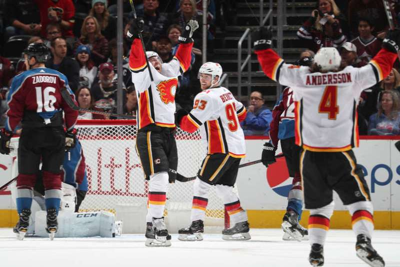 DENVER, CO - OCTOBER 13: Elias Lindholm #28 of the Calgary Flames celebrates with teammates Sam Bennett #93 and Rasmus Andersson #4 after scoring a goal against the Colorado Avalanche at the Pepsi Center on October 13, 2018 in Denver, Colorado. The Flames defeated the Avalanche 3-2 in overtime. (Photo by Michael Martin/NHLI via Getty Images)