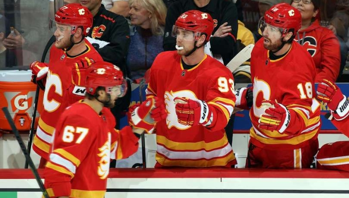 The Calgary Flames celebrate a first period goal against the Boston Bruins. Michael Frolik fist bumps Sam Bennett as he skates by the bench.
