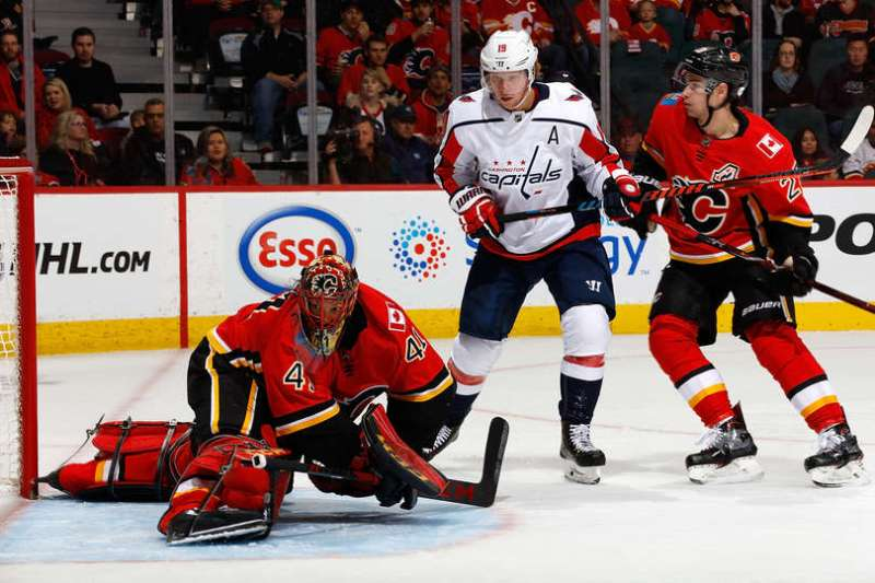 Mike Smith of the Calgary Flames makes a save while Sean Monahan defends against Niklas Backstrom.