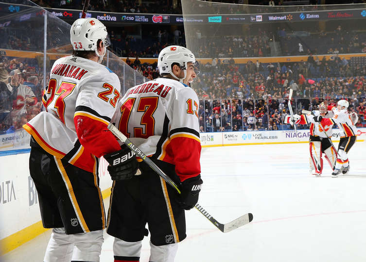 Johnny Gaudreau and Sean Monahan celebrate an overtime victory, David Rittich and Matthew Tkachuk celebrate in the background.