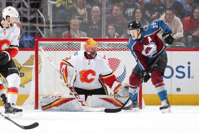 Nathan MacKinnon of the Colorado Avalanche attempts to deflect the puck on David Rittich of the Calgary Flames