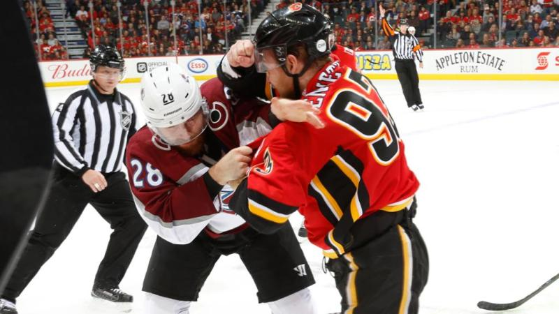 Sam Bennett of the Calgary Flames fights Ian Cole of the Colorado Avalanche.