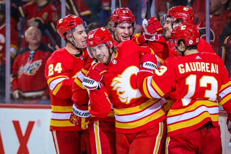 Elias Lindholm celebrates a goal with Johnny Gaudreau, Travis Hamonic, Sean Monahan, and Noah Hanifin.