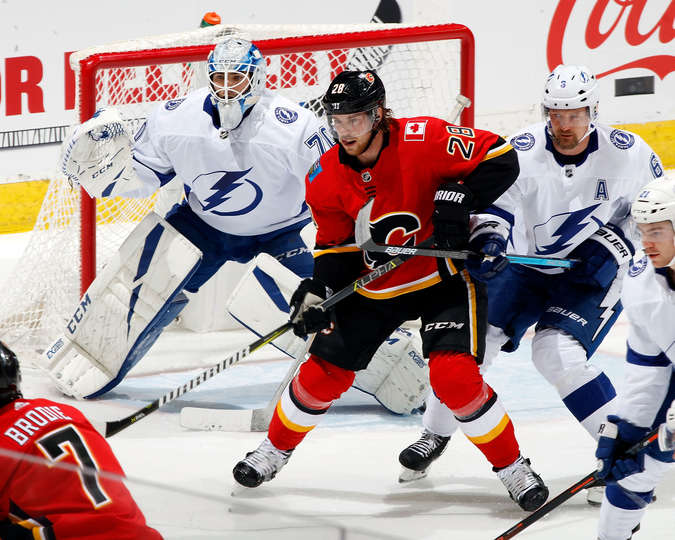 CALGARY, AB - DECEMBER 20: Elias Lindholm #28 of the Calgary Flames battles for position in front of Louis Domingue #70 and Anton Stralman #6 of the Tampa Bay Lightning during an NHL game on December 20, 2018 at the Scotiabank Saddledome in Calgary, Alberta, Canada. (Photo by Gerry Thomas/NHLI via Getty Images)