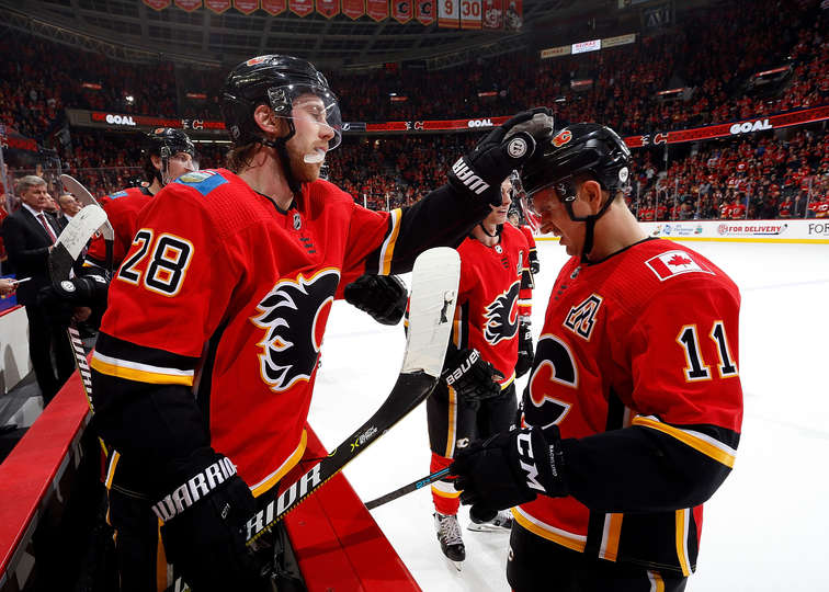 CALGARY, AB - DECEMBER 20: Elias Lindholm #28 and Mikael Backlund #11 of the Calgary Flames celebrate after a goal against the Tampa Bay Lightning during an NHL game on December 20, 2018 at the Scotiabank Saddledome in Calgary, Alberta, Canada. (Photo by Gerry Thomas/NHLI via Getty Images)