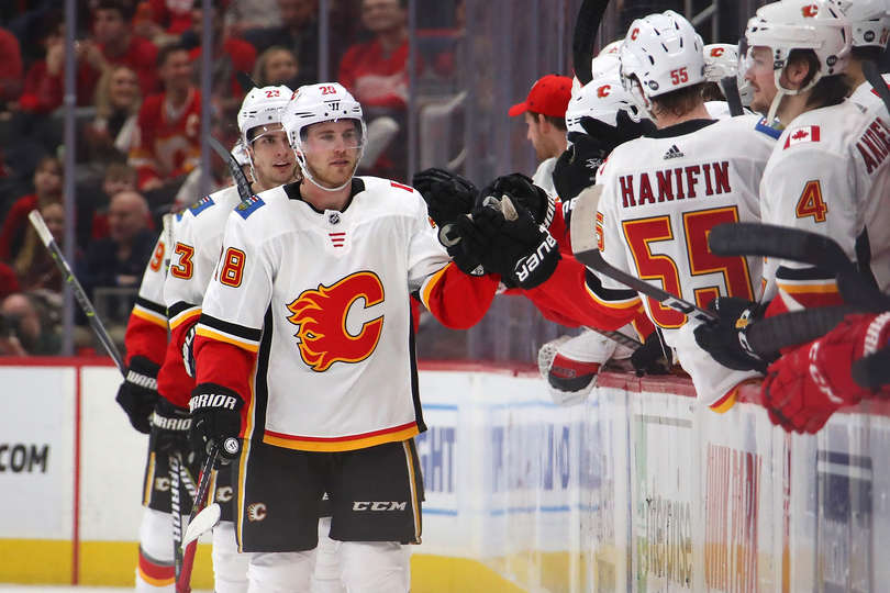 DETROIT, MICHIGAN - JANUARY 02: Elias Lindholm #28 of the Calgary Flames celebrates a second period goal with teammates while playing the Detroit Red Wings at Little Caesars Arena on January 02, 2019 in Detroit, Michigan. Calgary won the game 4-3. (Photo by Gregory Shamus/Getty Images)