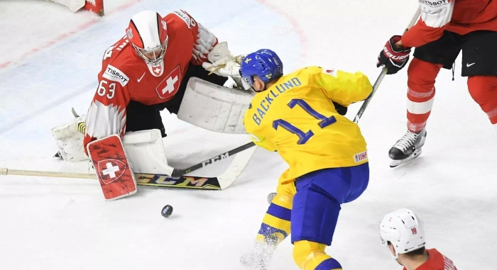 Team Sweden centre Mikael Backlund takes a shot against Swiss goaltender Leonardo Genoni