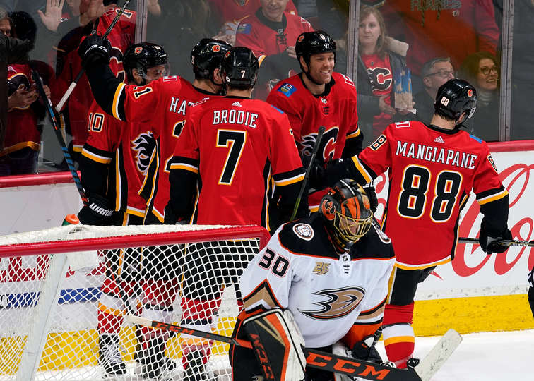 CALGARY, AB - FEBRUARY 22: Andrew Mangiapane #88, T.J. Brodie #7 and Dalton Prout #6 of the Calgary Flames celebrate a goal against the Anaheim Ducks during an NHL game on February 22, 2019 at the Scotiabank Saddledome in Calgary, Alberta, Canada. (Photo by Gerry Thomas/NHLI via Getty Images)