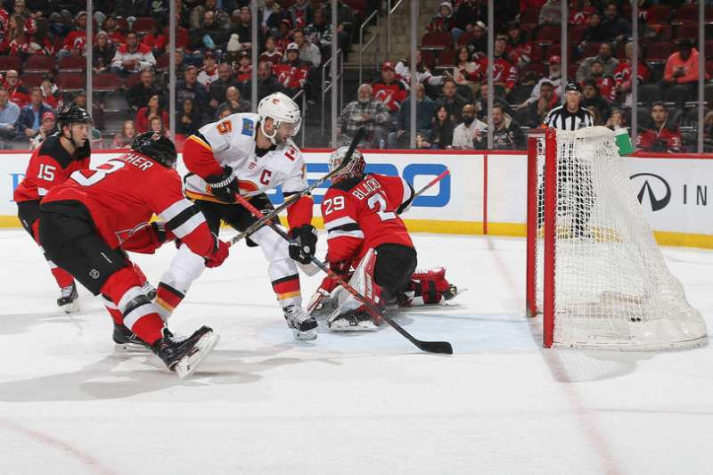 NEWARK, NJ - FEBRUARY 27: Mark Giordano #5 of the Calgary Flames scores a goal on Mackenzie Blackwood #29 of the New Jersey Devils during the game at Prudential Center on February 27, 2019 in Newark, New Jersey. (Photo by Andy Marlin/NHLI via Getty Images)