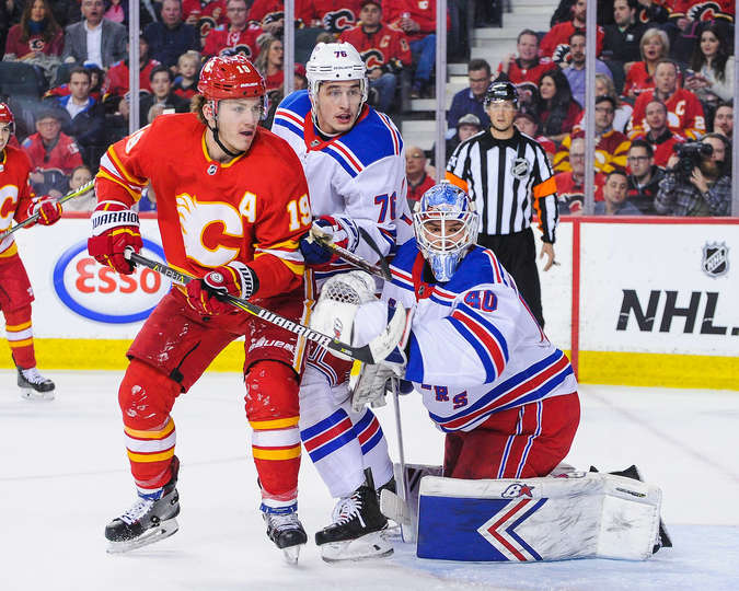CALGARY, AB - MARCH 15: Matthew Tkachuk #19 of the Calgary Flames looks for an opportunity in front of the net of Alexandar Georgiev #40 of the New York Rangers during an NHL game at Scotiabank Saddledome on March 15, 2019 in Calgary, Alberta, Canada. (Photo by Derek Leung/Getty Images)