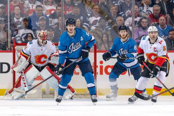WINNIPEG, MB - MARCH 16: Mark Scheifele #55 and Kyle Connor #81 of the Winnipeg Jets stand between goaltender Mike Smith #41 and Mark Giordano #5 of the Calgary Flames as they keep an eye on the play during first period action at the Bell MTS Place on March 16, 2019 in Winnipeg, Manitoba, Canada. (Photo by Jonathan Kozub/NHLI via Getty Images)