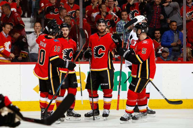 CALGARY, AB - MARCH 21: Andrew Mangiapane #88, TJ Brodie #7 and teammates of the Calgary Flames celebrate a goal against the Ottawa Senators during an NHL game on March 21, 2019 at the Scotiabank Saddledome in Calgary, Alberta, Canada. (Photo by Gerry Thomas/NHLI via Getty Images)