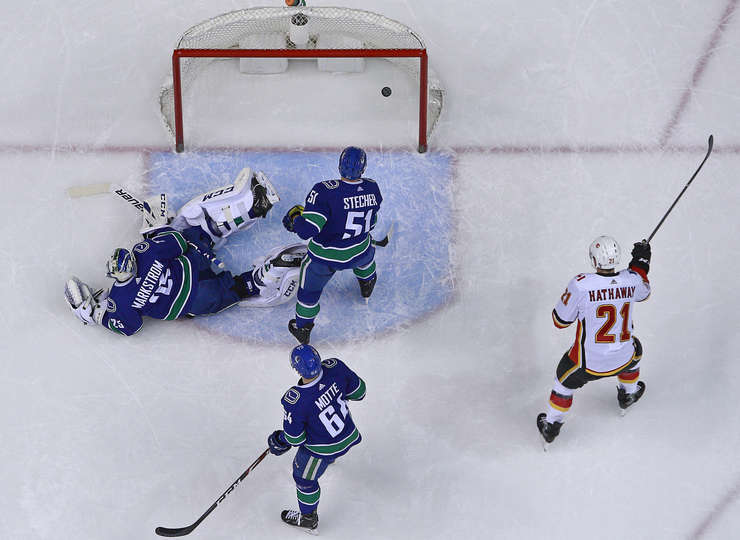 VANCOUVER, BC - MARCH 23: Jacob Markstrom #25 of the Vancouver Canucks looks on dejected as Garnet Hathaway #21 of the Calgary Flames celebrates a Calgary goal during their NHL game at Rogers Arena March 23, 2019 in Vancouver, British Columbia, Canada. (Photo by Jeff Vinnick/NHLI via Getty Images)