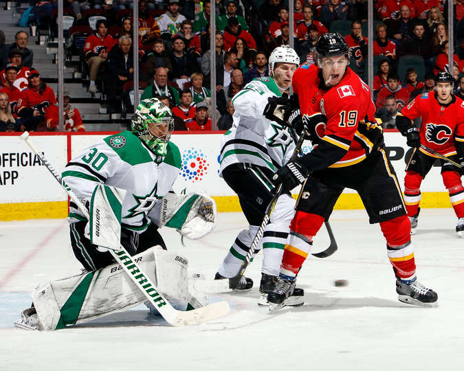 CALGARY, AB - MARCH 27: Matthew Tkachuk #19 of the Calgary Flames tries to tip the puck past Ben Bishop #30 of the Dallas Stars during an NHL game on March 27, 2019 at the Scotiabank Saddledome in Calgary, Alberta, Canada. (Photo by Gerry Thomas/NHLI via Getty Images)