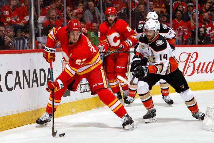 CALGARY, AB - MARCH 29: Sean Monahan #23 of the Calgary Flames skates against Adam Henrique #14 of the Anaheim Ducks during an NHL game on March 29, 2019 at the Scotiabank Saddledome in Calgary, Alberta, Canada. (Photo by Gerry Thomas/NHLI via Getty Images)