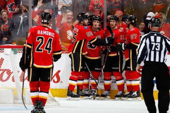 CALGARY, AB - MARCH 19: Matthew Tkachuk #19, Noah Hanifin #55 and teammates of the Calgary Flames celebrate a goal against the Columbus Blue Jackets during an NHL game on March 19, 2019 at the Scotiabank Saddledome in Calgary, Alberta, Canada. (Photo by Gerry Thomas/NHLI via Getty Images)