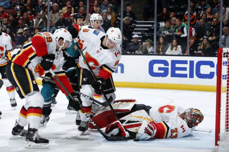 ANAHEIM, CA - APRIL 3: David Rittich #33 of the Calgary Flames makes the save with help from Juuso Valimaki #8 and Alan Quine #89 during the game against the Anaheim Ducks on April 3, 2019 at Honda Center in Anaheim, California. (Photo by Debora Robinson/NHLI via Getty Images)