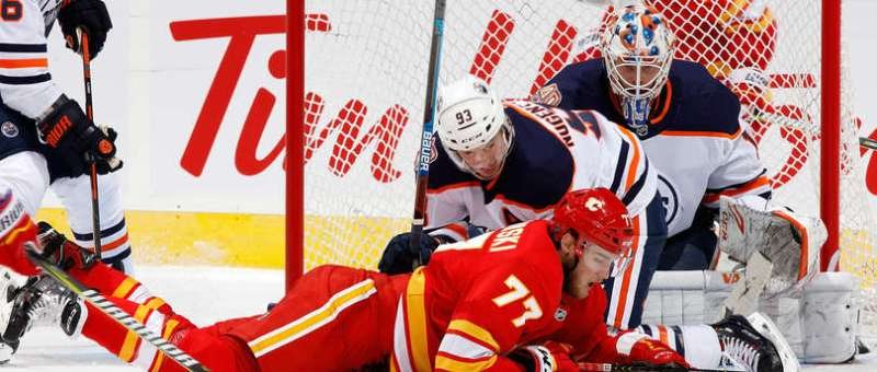 CALGARY, AB - APRIL 6: Mark Jankowski #77 of the Calgary Flames is knocked down by Ryan Nugent-Hopkins of the Edmonton Oilers during an NHL game on April 6, 2019 at the Scotiabank Saddledome in Calgary, Alberta, Canada. (Photo by Gerry Thomas/NHLI via Getty Images)