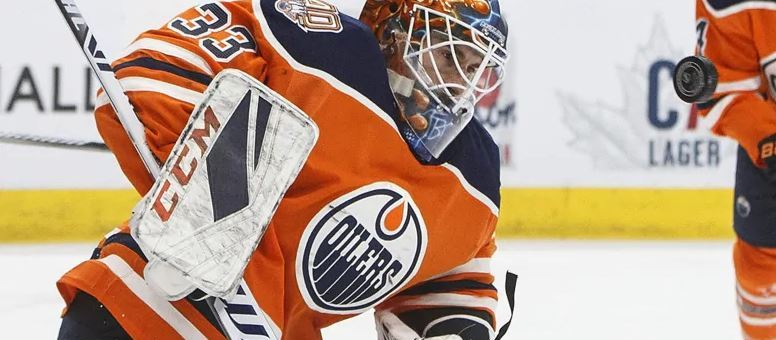 Cam Talbot of the Edmonton Oilers tracking a hockey puck mid-game. Photo by Jason Franson/The Canadian Press.