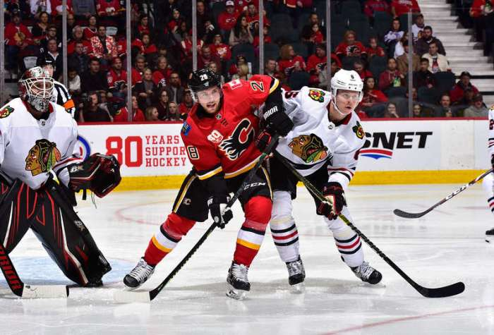 CALGARY, AB - FEBRUARY 15: Elias Lindholm #28 of the Calgary Flames battles against Olli Maatta #6 of the Chicago Blackhawks at Scotiabank Saddledome on February 15, 2020 in Calgary, Alberta, Canada. (Photo by Terence Leung/NHLI via Getty Images)