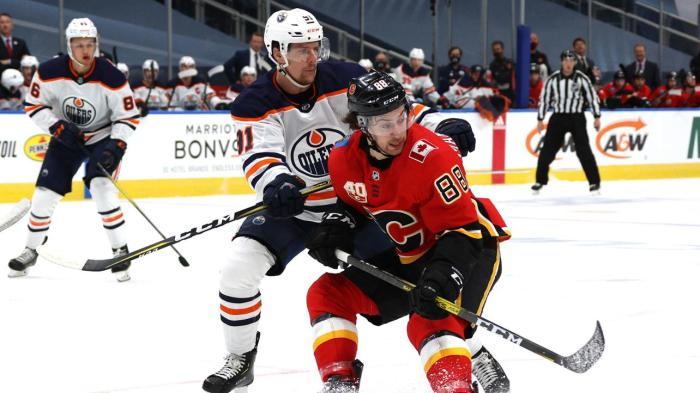 EDMONTON, ALBERTA - JULY 28: Gaetan Haas #91 of the Edmonton Oilers battles with Andrew Mangiapane #88 of the Calgary Flames during the first period of the exhibition game prior to the 2020 NHL Stanley Cup Playoffs at Rogers Place on July 28, 2020 in Edmonton, Alberta. (Photo by Dave Sandford/NHLI via Getty Images)