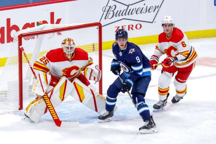 WINNIPEG, MB - JANUARY 14: Andrew Copp #9 of the Winnipeg Jets stands between goaltender Jacob Markstrom #25 and Juuso Valimaki #6 of the Calgary Flames as they keep an eye on the play during first period action at the Bell MTS Place on January 14, 2021 in Winnipeg, Manitoba, Canada. (Photo by Darcy Finley/NHLI via Getty Images)
