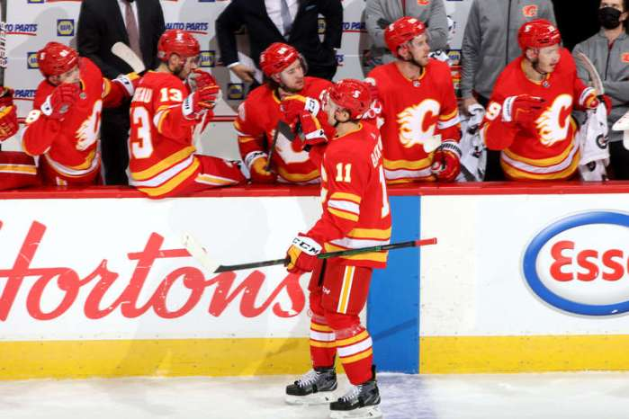 CALGARY, ALBERTA - JANUARY 18: Mikael Backlund #11 and teammates of the Calgary Flames celebrate a goal against the Vancouver Canucks at Scotiabank Saddledome on January 18, 2021 in Calgary, Alberta. (Photo by Gerry Thomas/NHLI via Getty Images)