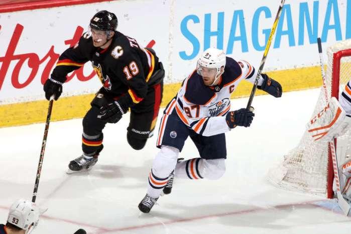CALGARY, ALBERTA - FEBRUARY 06: Connor McDavid #97 of the Edmonton Oilers skates against Matthew Tkachuk #19 of the Calgary Flames at Scotiabank Saddledome on February 06, 2021 in Calgary, Alberta. (Photo by Gerry Thomas/NHLI via Getty Images)
