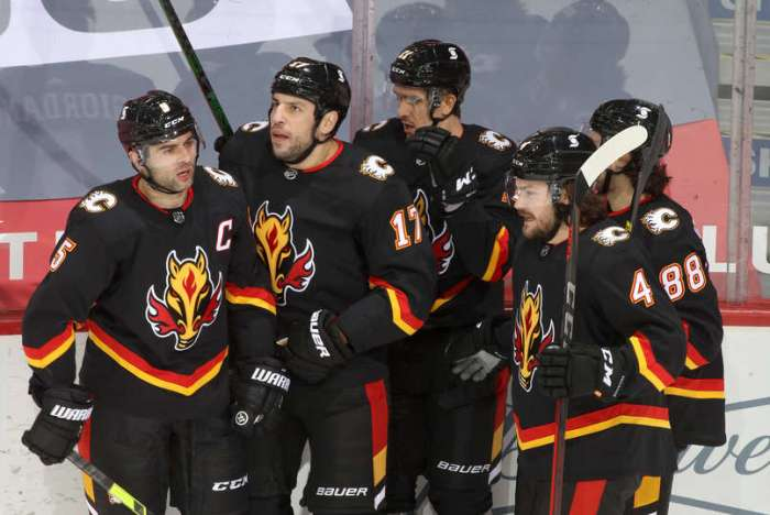 CALGARY, ALBERTA - FEBRUARY 06: Milan Lucic #17, Rasmus Andersson #4 and teammates of the Calgary Flames celebrate a goal against the Edmonton Oilers at Scotiabank Saddledome on February 06, 2021 in Calgary, Alberta. (Photo by Gerry Thomas/NHLI via Getty Images)